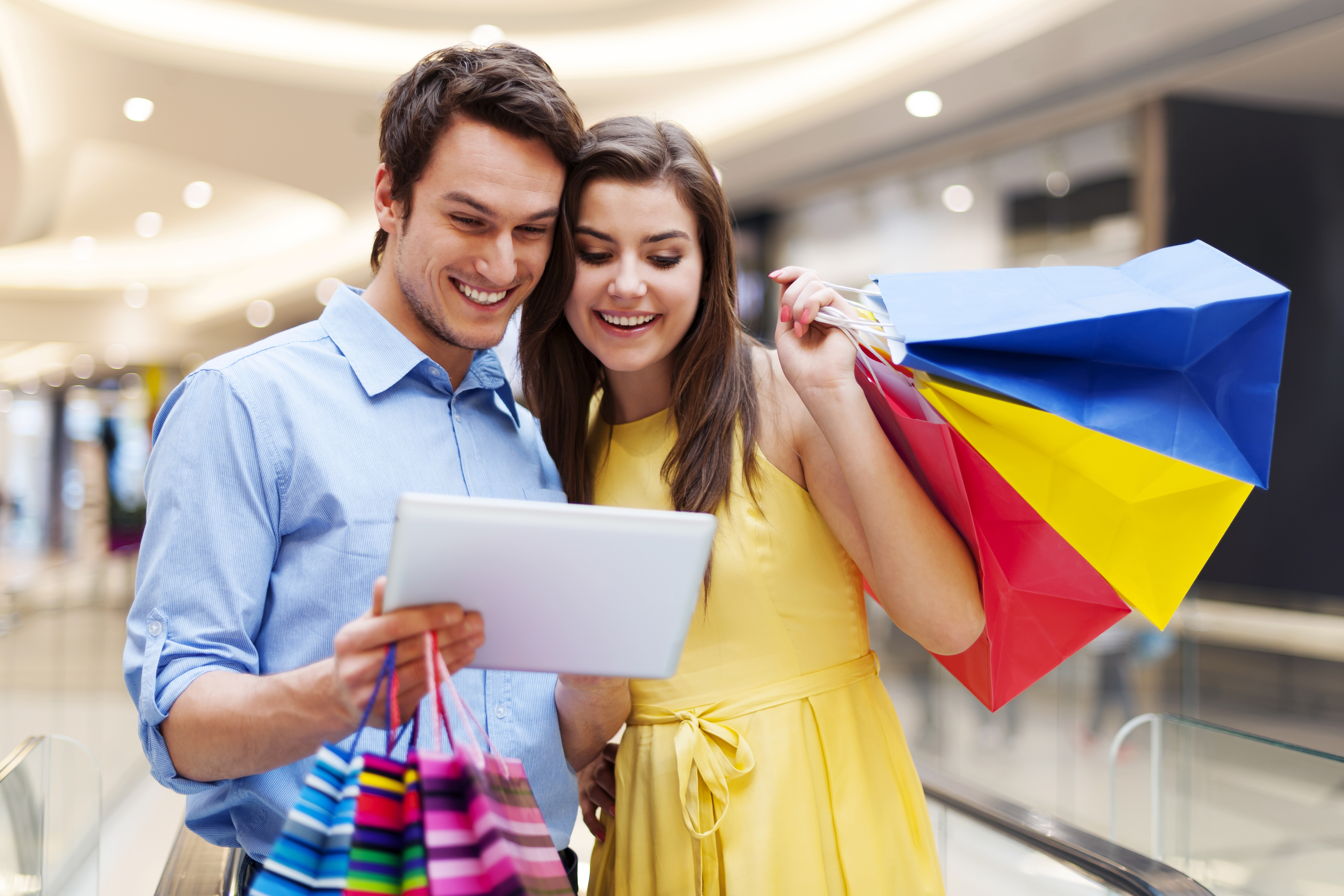 Happy couple using s digital tablet in the shopping mall